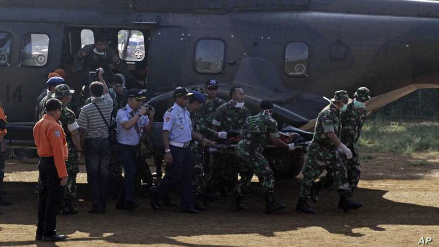 Indonesian soldiers carry a victim of Wednesday's plane crash at Cijeruk in Bogor, West Java, Indonesia, Saturday, May 12, 2012.