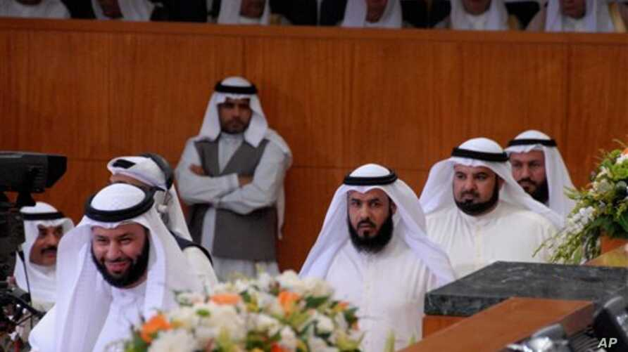 FILE - Abdullah al-Barghash, second from left, returns to parliamentary session after walking out in protest of two female cabinet members that were not dressed according to strict Islamic codes, Kuwait, June 1, 2008.