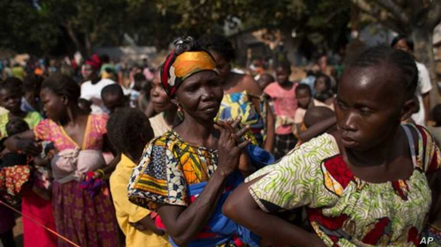 Women wait in line to have their children vaccinated against measles, at a makeshift camp housing people displaced by violence at a monastery in the Boy Rabe district of Bangui, Central African Republic, Sunday, Jan. 5, 2014. Concerned that crowded a