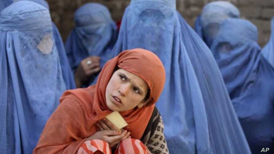 An Afghan girl waits with a group of women for food distribution by a German humanitarian organization in downtown Kunduz, Afghanistan, Dec.14, 2010.