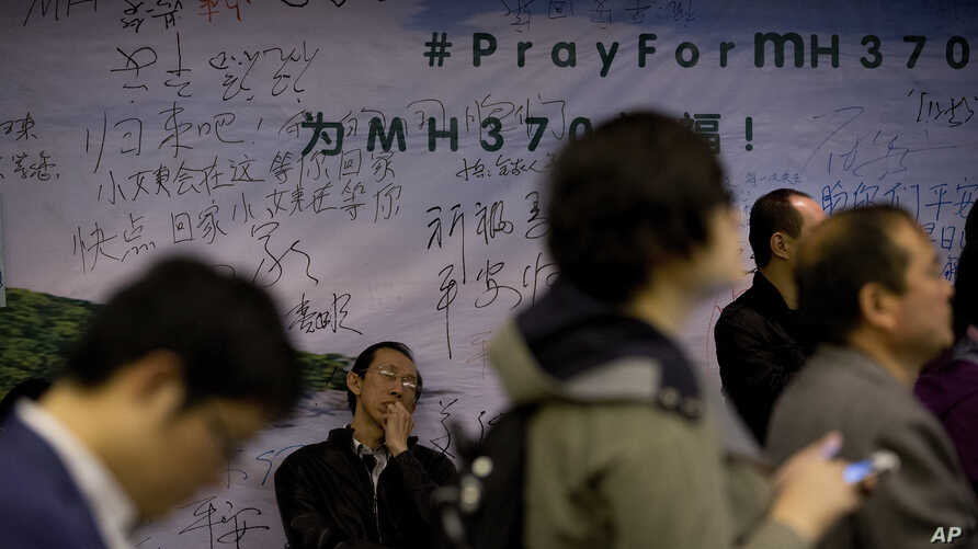 A relative of Chinese passengers aboard Flight MH370 takes a nap against the wall displaying messages of wishes for the passengers during a briefing held by Malaysia officials at a hotel in Beijing, April 11, 2014.