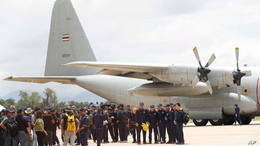 Thai Navy SEALs and military personnel take a group picture before they board a plane at the airport in Chiang Rai, northern Thailand, Thursday, July 12, 2018.