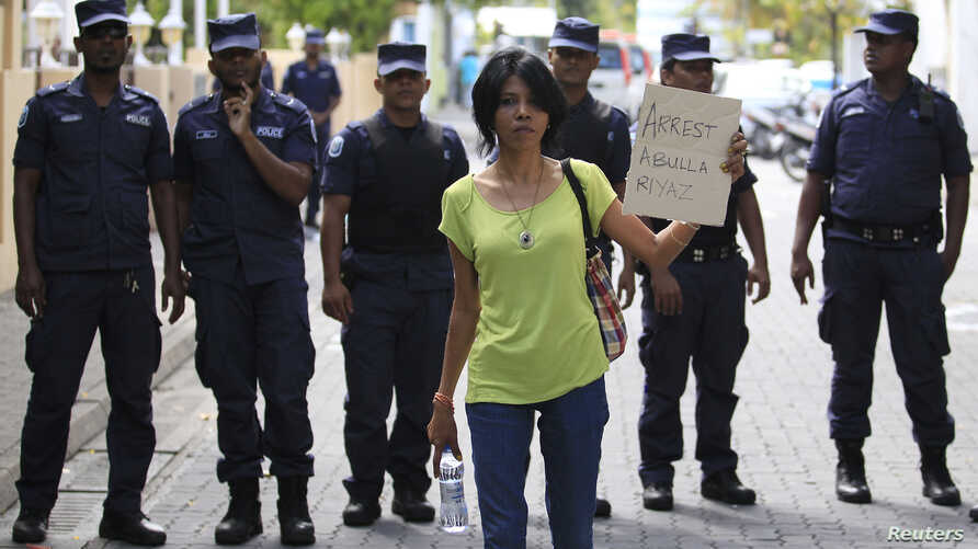 A supporter of presidential candidate Mohamed Nasheed, who was ousted as president in 2012, holds up a placard during a protest against the Maldives police, in Male, Oct. 19, 2013.