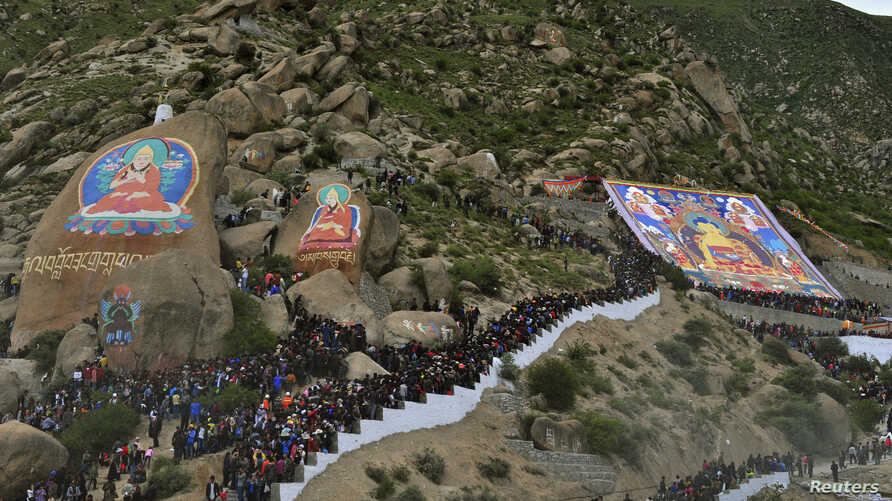 Tibetan Buddhists and tourists view a giant thangka, a religious silk embroidery or painting displaying the Buddha portrait, during the Shoton Festival at Drepung Monastery in Lhasa, Tibet Autonomous Region August 6, 2013.