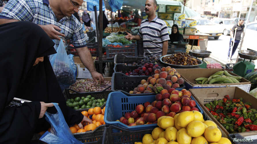 FILE - Residents shop for fruits and vegetables at a market in Baghdad's Karrada district. Iraq relies on imports from neighbors like Iran, Syria and Turkey for much of its consumer goods.