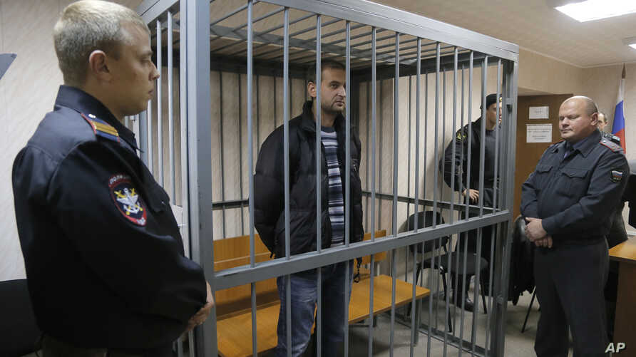 A police officers guards a cage with Greenpeace activist  Ruslan Yakushev of Ukraine in a court room in Murmansk, Russia, Thursday, Sept. 26, 2013. A Russian court on Thursday jailed the activist who was part of the 30-member Greenpeace team protesti
