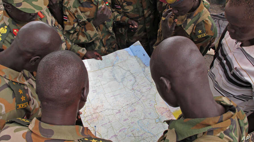 Soldiers from the Sudan People's Liberation Army (SPLA) examine a map at the front line position in Pana Kuach, Unity State, South Sudan, May 11 2012.