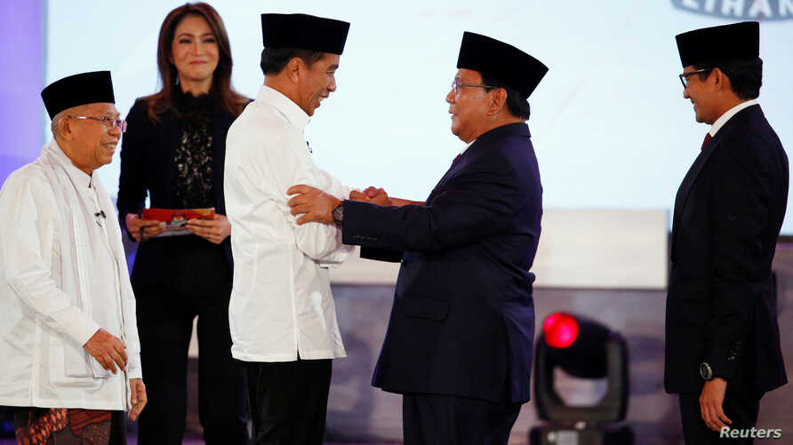 Indonesia's presidential candidate Joko Widodo shakes hands with his opponent Prabowo Subianto as their running mates Ma'ruf Amin and Sandiaga Uno smile after a televised debate in Jakarta, Indonesia, Jan. 17, 2019.