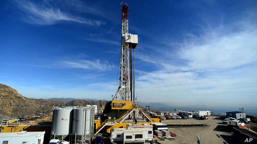 FILE - Crews work on stopping a gas leak at a relief well at the Aliso Canyon facility above the Porter Ranch area of Los Angeles, Dec. 9, 2015. The gas-storage facility had spewed methane uncontrollably for almost four months, driving thousands of f