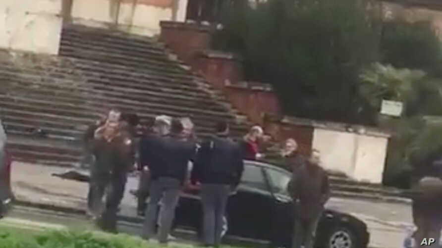 People gather where witnesses say a shooter was arrested in Macerata, Italy, Feb. 3, 2018, in this still image obtained from social media video. (Marcelo Mancini via REUTERS)