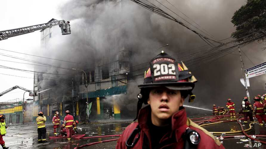 Firefighters try to extinguish a fire at a warehouse in Lima, Peru, June 23, 2017.
