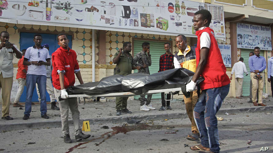 Medical workers remove the body of a civilian who was killed in a car bomb explosion near the parliament building in the capital Mogadishu, Somalia, March 25, 2018.