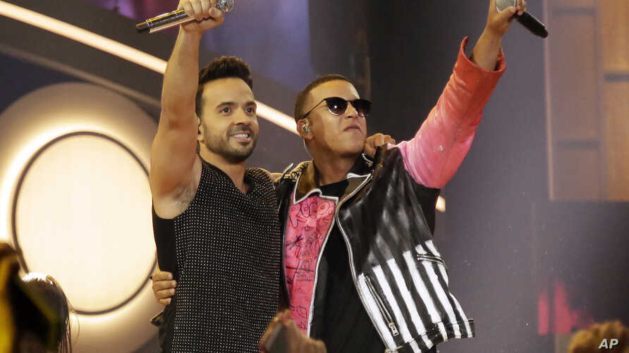 """FILE - This April 27, 2017, photo shows singers Luis Fonsi, left, and Daddy Yankee during the Latin Billboard Awards in Coral Gables, Florida. The success of their hit song """"Despacito,"""" has stretched beyond its Latin audience, becoming the year's m..."""