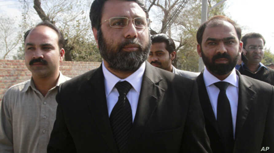 Asad Manzoor Butt (C) and Numan Attique (R), lawyers for the families of the two men killed by U.S. contractor Raymond Davis, walk together with the victim's brother, Imran Haider (L), after attending Davis' hearing in Lahore, March 8, 2011