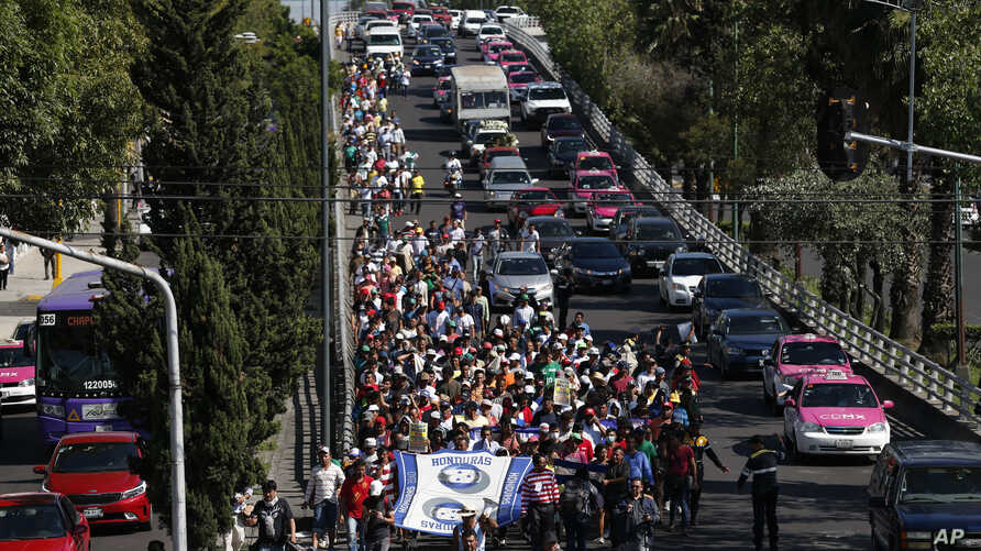 A group of Central American migrants, some of the thousands participating in caravans trying to reach the U.S. border, undertake an hours-long march to the office of the U.N. human rights body in Mexico City, Nov. 8, 2018. Members of the caravan dema...