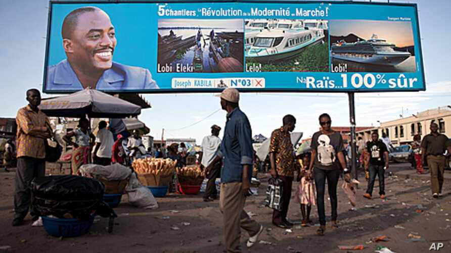 People walk under a giant poster showing Democratic Republic of the Congo 's President and candidate for a second term Joseph Kabila, in Kinshasa, November 7, 2011.