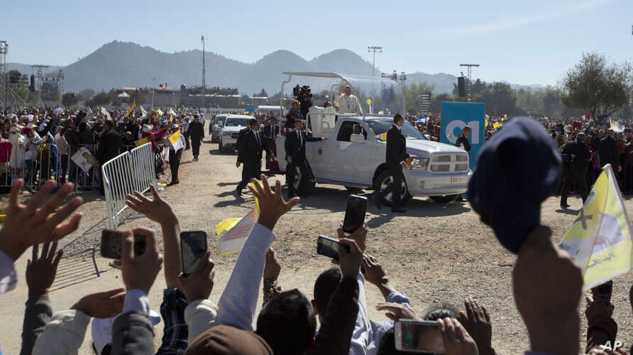 People wave to Pope Francis as he arrives to celebrate Mass in San Cristobal de las Casas, Mexico, Feb. 15, 2016.