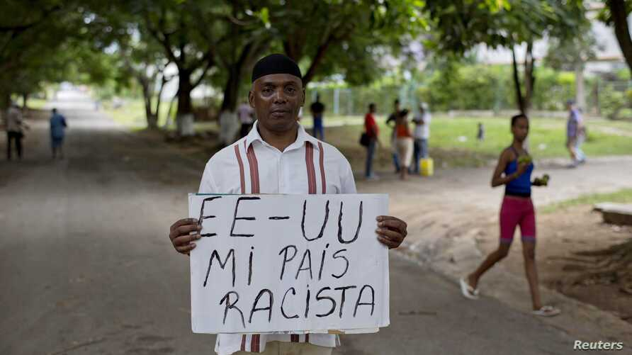 """U.S. citizen William Potts poses with sign that says """"USA my racist country""""  in Spanish, Havana, Cuba,  Oct. 25, 2013."""