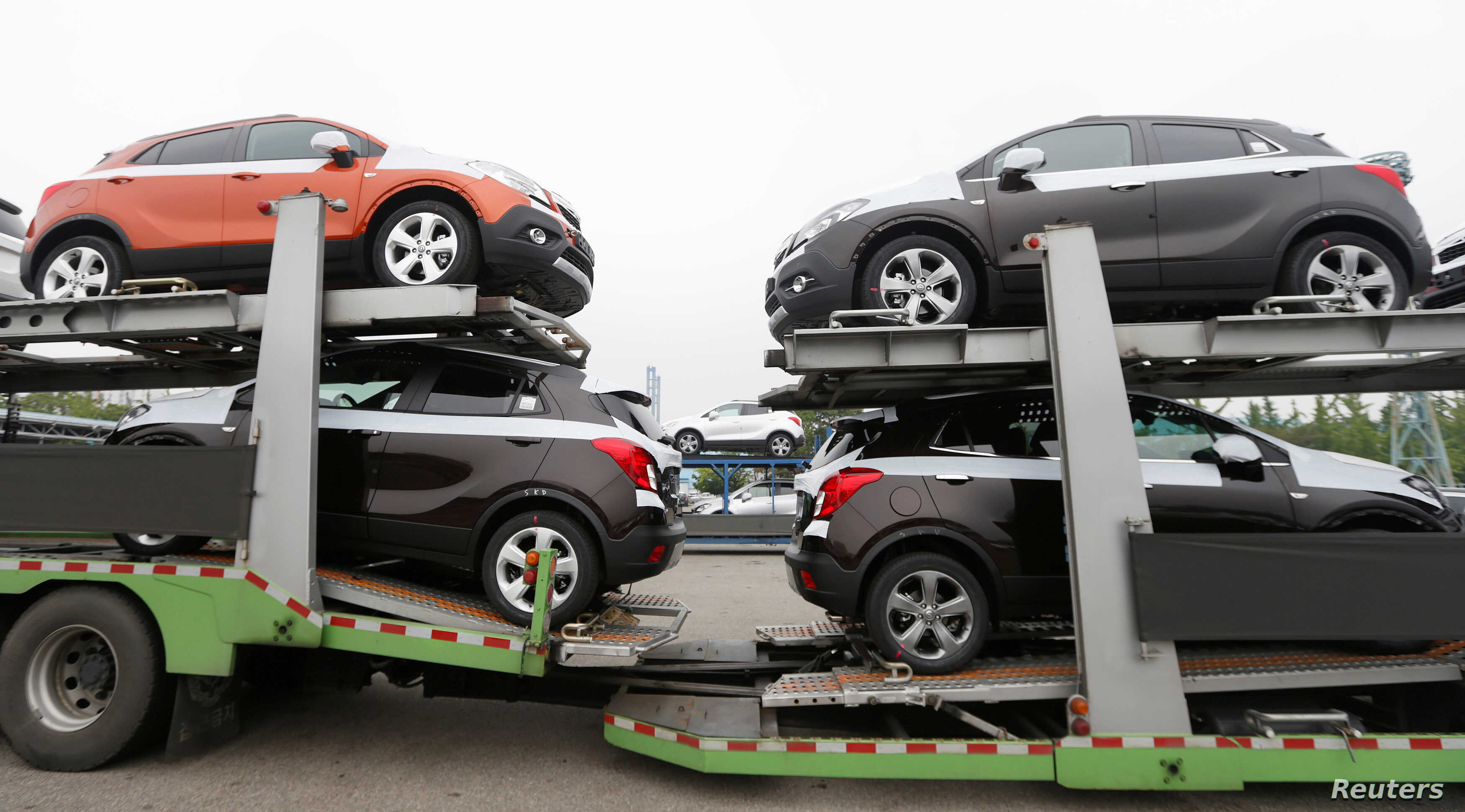 FILE - Cars made by GM Korea are seen on trucks in a yard of GM Korea's Bupyeong plant before they are transported to a port for export, in Incheon, west of Seoul, Aug. 9, 2013.