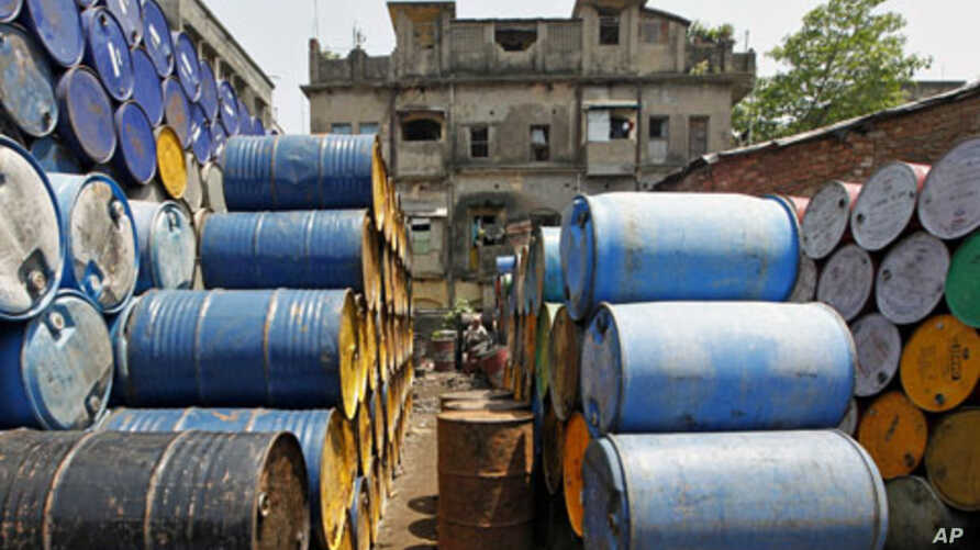 A laborer works amid oil containers at a wholesale fuel market in Kolkata, India, April 7, 2011
