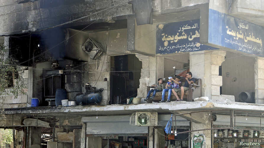 Residents sit on the balcony of a damaged building in Aleppo's al-Shaar neighborhood, Syria, August 2015.