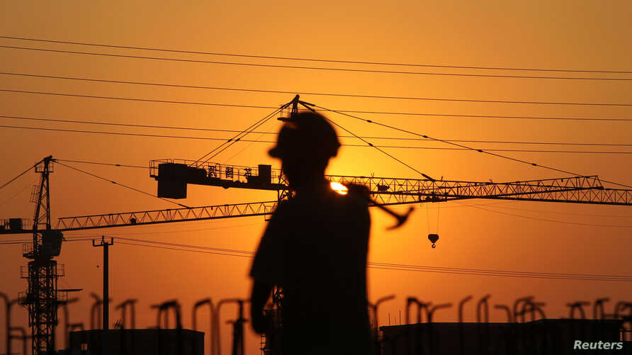 A worker walks with a hammer past a residential construction site during sunset in Nantong, Jiangsu province, China, Aug. 6, 2013.
