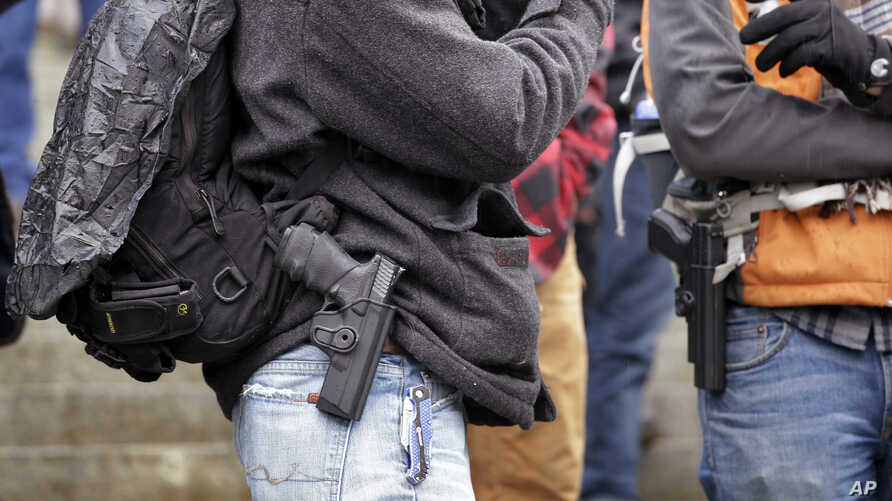 FILE - Men stand with pistols strapped at their sides at a gun rights rally on the steps of the Washington state capitol, Jan. 15, 2016, in Olympia, Wash.