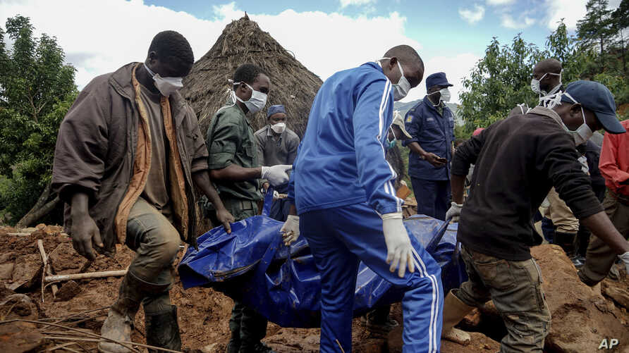 Men retrieve the body of a teenager killed by mudslides triggered by Cyclone Idai, in Chimanimani, Zimbabwe, March 22, 2019.