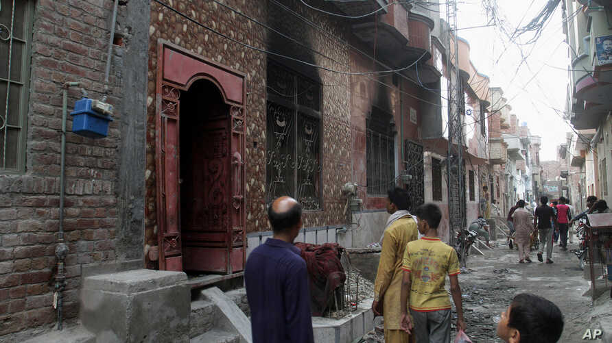 Residents look at a  house of a family belonging to the Ahmadi sect, which was torched by angry mob in Gujranwala, Pakistan, July 28, 2014.