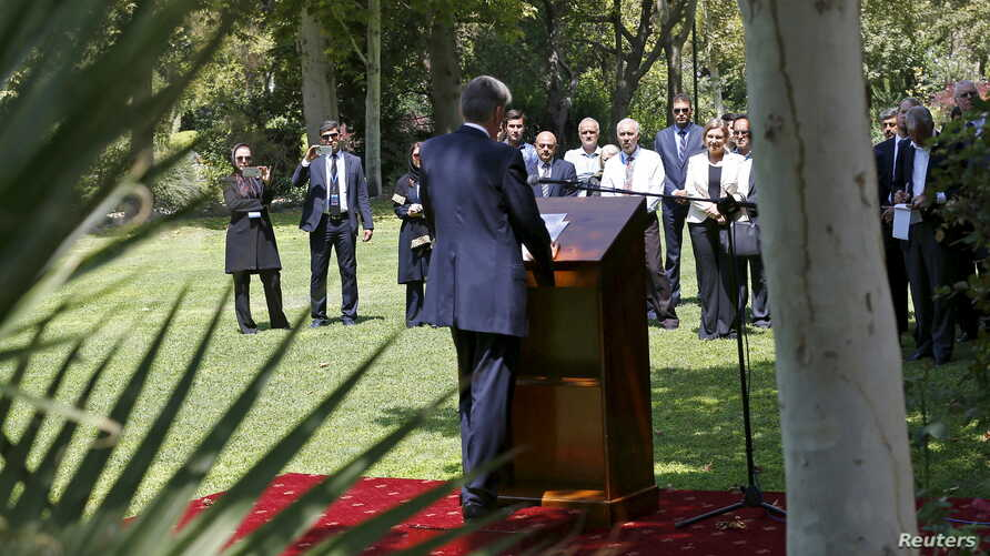 Embassy workers listen to Britain's Foreign Secretary Philip Hammond during the reopening of the British Embassy in Tehran, Iran, Aug. 23, 2015.