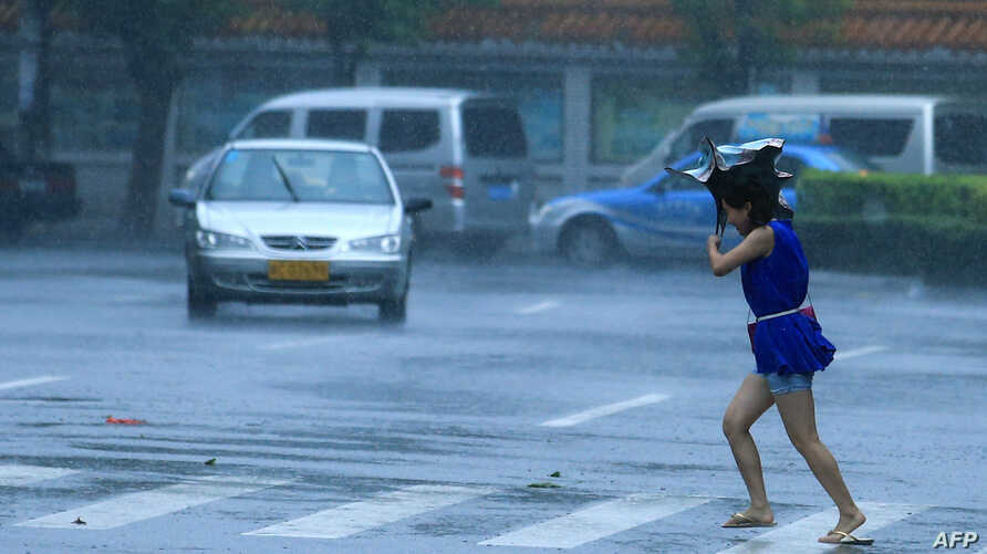 A woman walks on a street in heavy rain and strong wind in Haikou, south China's Hainan province, July 18, 2014.