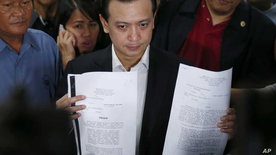Philippine opposition Sen. Antonio Trillanes IV holds copies of the decision of the trial court granting him amnesty during a news conference at the Philippine Senate in suburban Pasay city, south of Manila, Philippines, Sept. 5, 2018.