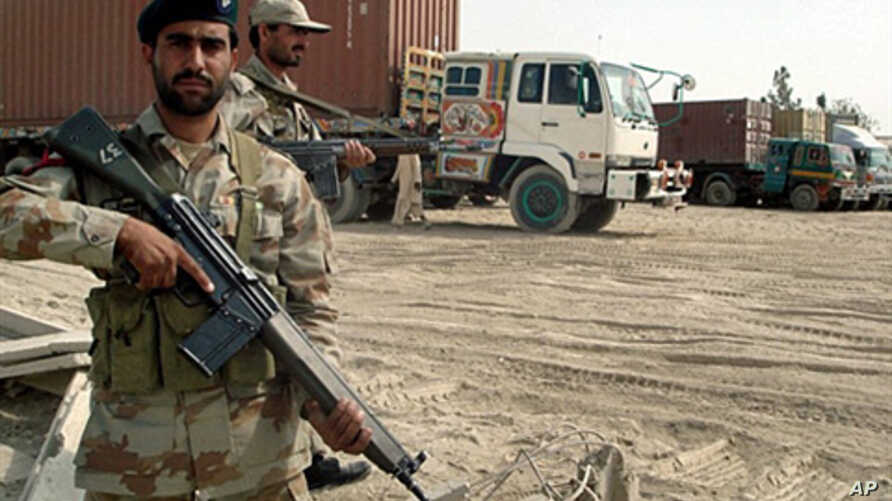 Pakistani paramilitary soldiers stand alongside trucks carrying NATO supplies at the border town of Chamam, Pakistan, 30 Sept. 2010