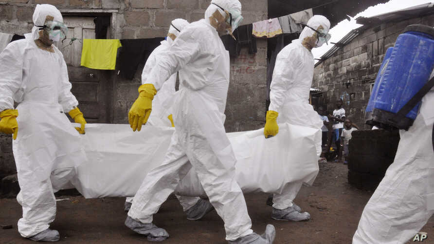 Health workers carry the body of a woman that they suspect died from the Ebola virus, as children, right rear, watch in a area known as Clara Town in Monrovia, Liberia, Sept. 10, 2014.