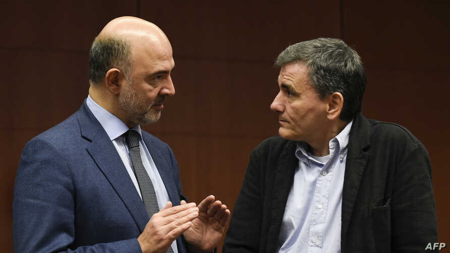 European Commissioner for Economic and Financial Affairs, Taxation and Customs Pierre Moscovici (L) talks with  Greek Finance Minister Euclid Tsakalotos (R) prior to an Eurogroup meeting on Nov. 23, 2015 at EU Headquarters in Brussels.