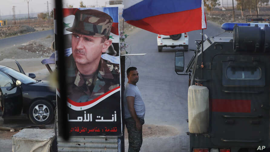 A Syrian army soldier stands at a checkpoint as a Russian military police vehicle, right, passes by near the village of Almajdiyeh, Syria, Aug. 14, 2018.