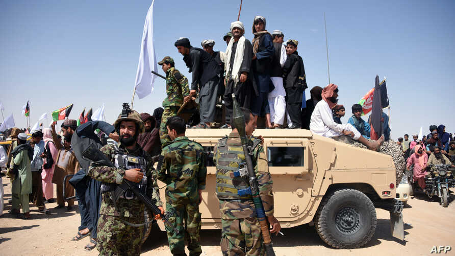 In this photo taken on June 17, 2018, Afghan Taliban militants and residents stand on a armoured Humvee vehicle of the Afghan National Army (ANA) as they celebrate a ceasefire on the third day of Eid in Maiwand district of Kandahar province.
