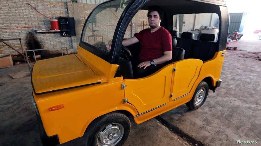 """Ahmed Saeed Omar, 35, looks on inside his new """"Mini-Car-Egypt"""" car at his workshop, near Egypt's pyramids of Giza, in Kerdasa, Egypt, May 10, 2017."""