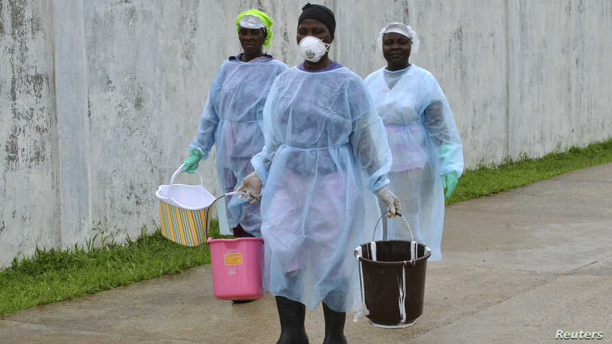 Health workers carry buckets of disinfectant at the newly-constructed Island Clinic and Ebola treatment center in Monrovia, Liberia, September 25, 2014. REUTERS/James Giahyue (LIBERIA - Tags: POLITICS HEALTH) - RTR47PZA