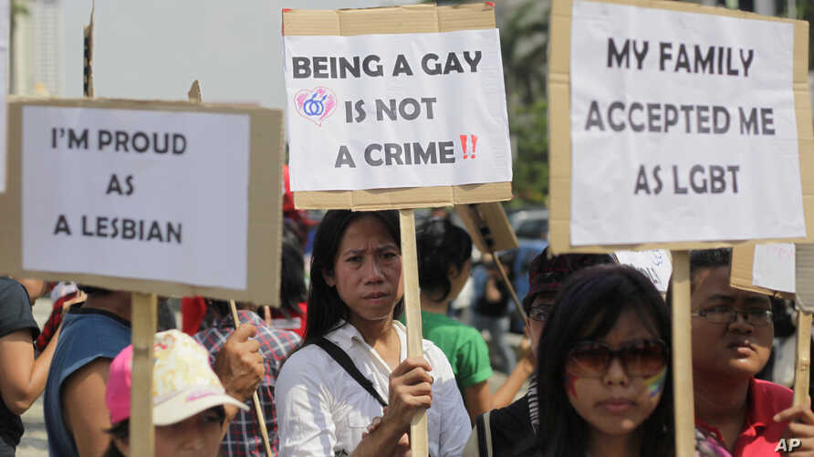 FILE - Indonesian gay activists hold posters during a protest demanding equality for LGBT (Lesbian, gay, bisexual and transgender) people in Jakarta, Indonesia, Saturday, May 21, 2011.