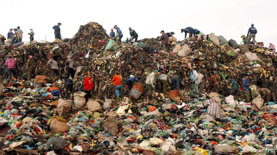 Scavengers search for recyclable materials to be sold to recycling centers, at the Nam Son garbage dump, north of Hanoi, Vietnam, June 4, 2013.