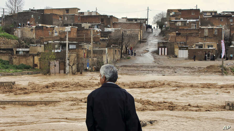 A man watches as floodwaters hit the city of Khorramabad in the western province of Lorestan, Iran, April 1, 2019.