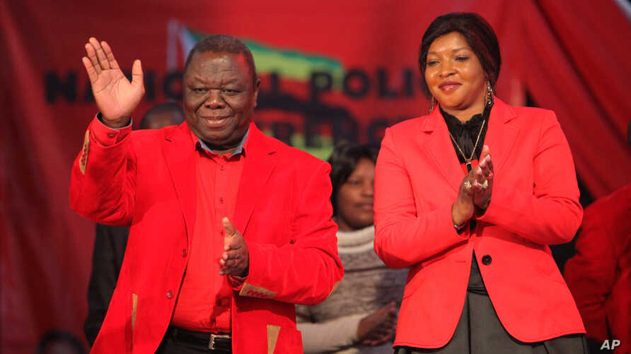 Zimbabwean Prime Minister and Movement for Democractic Change (MDC) President Morgan Tsvangirai, left, and his wife Elizabeth greet the audience on the first day of the party's National Policy Conference in Harare, May 17, 2013.