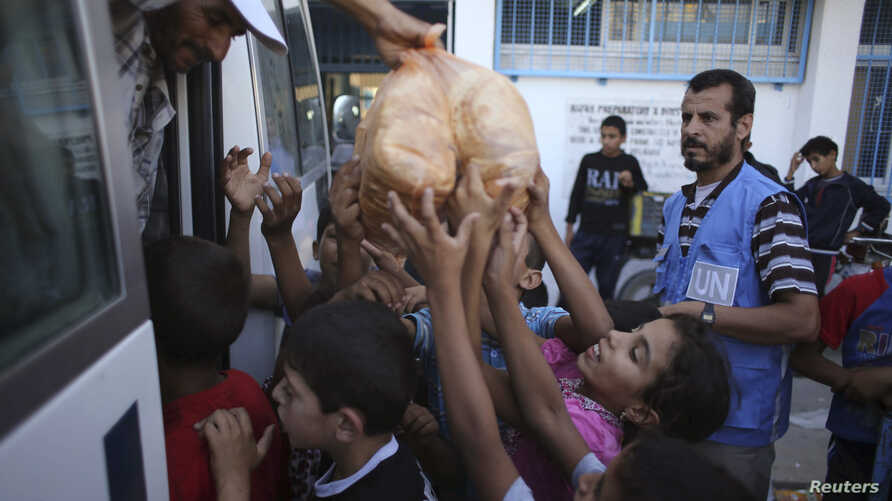 Palestinian children receive bags of bread from United Nations workers at a U.N.-run school in Rafah in the southern Gaza Strip July 19, 2014.
