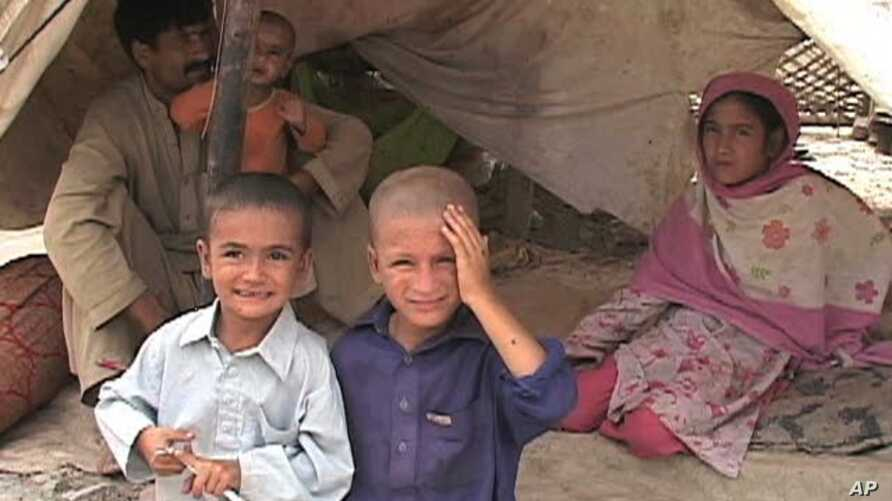 These Pakistani flood victims have set up camp near a busy roadway