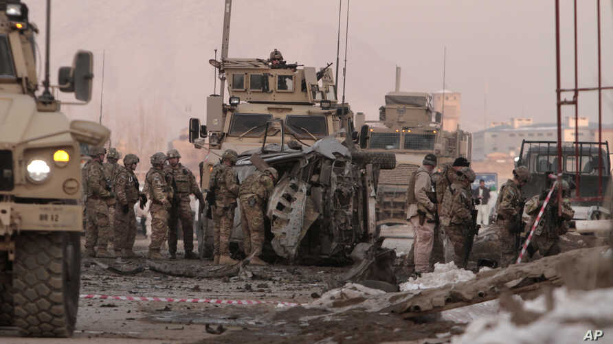 U.S. soldiers search the site where a suicide attacker rammed a car bomb into a NATO convoy, killing two foreign civilian contractors, in the Afghan capital Kabul, Afghanistan, Feb. 10, 2014.