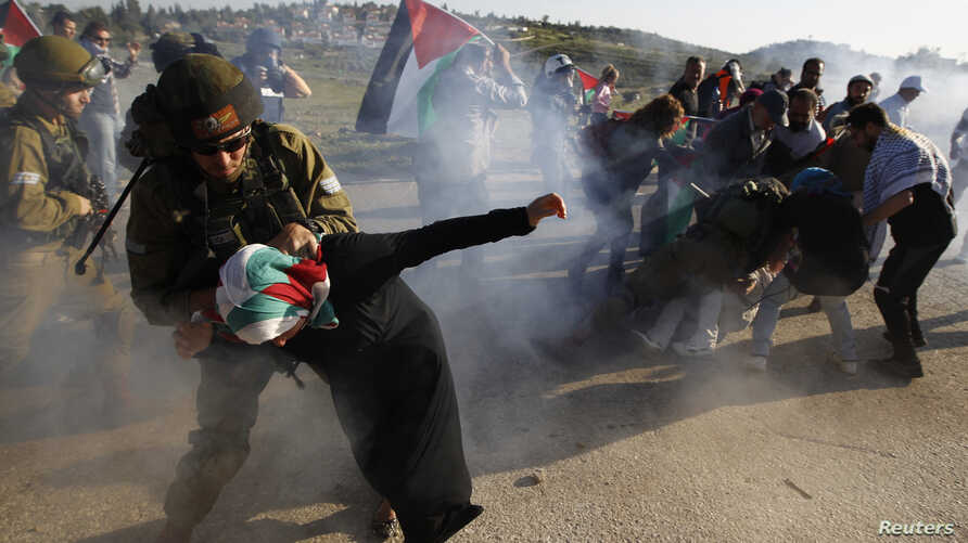 An Israeli soldier detains a Palestinian woman during a protest calling for the opening an Israeli-closed gate leading to Nabi Saleh village, near the West Bank city of Ramallah April 14, 2014.