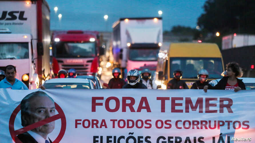 "Protestors block the Presidente Dutra highway during a strike against Brazilian Social Welfare reform project from government, in Sao Jose dos Campos, Brazil March 15, 2017. The banner reads: ""Out, Temer. Out, all corrupt. Elections now."""