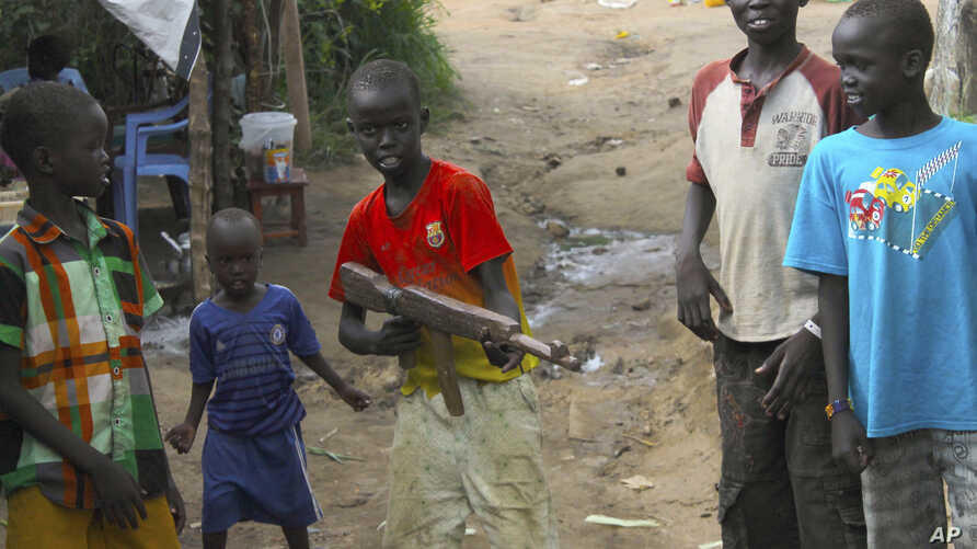 FILE--A group of children at the U.N. protection of Civilians site in Juba, South Sudan, play with a toy gun, July 25, 2016.