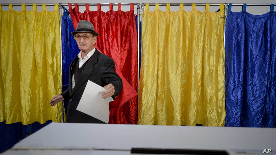 A man exits the voting booth, in Bucharest, Romania, Saturday, Oct. 6, 2018. Two days of voting on a constitutional amendment that would make it harder to legalize same-sex marriage has started in Romania.